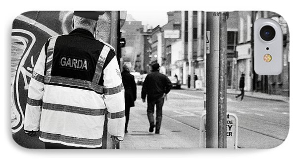 irish garda police sergeant on foot patrol in dublin city centre Ireland IPhone Case by Joe Fox