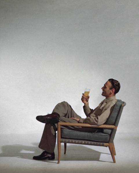A Man Sitting In An Armchair With A Drink Poster