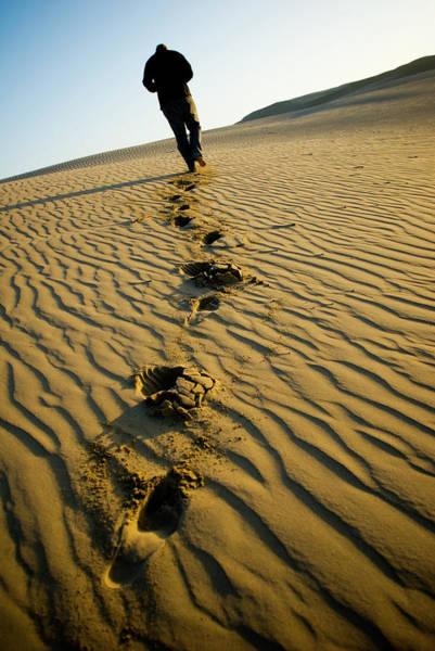 A Man Walks Through Sand Dunes Poster