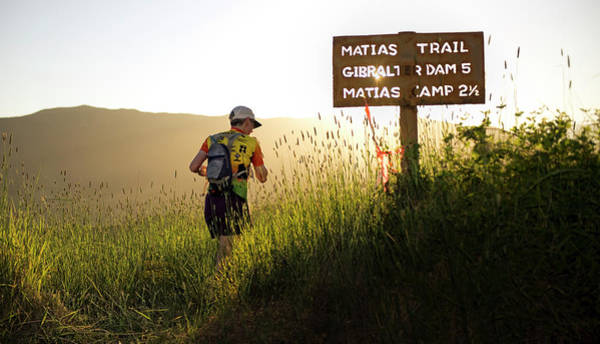 A Trail Runner Passes A Sign And Trail Poster