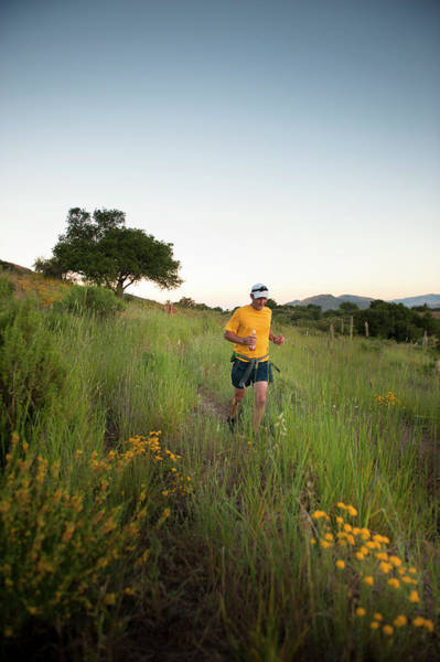 A Trail Runner Passes Wildflowers Poster