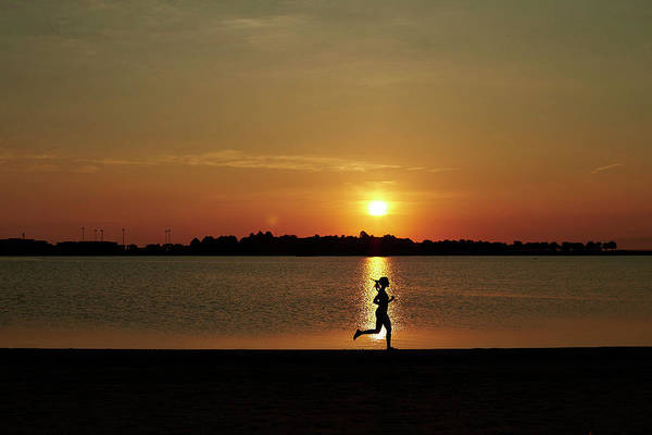 A Woman Running At Sunrise Poster