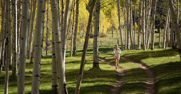 A Young Woman Runs Through A Wide Aspen Poster