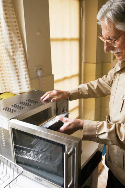 Elderly Man Using A Microwave Oven Poster