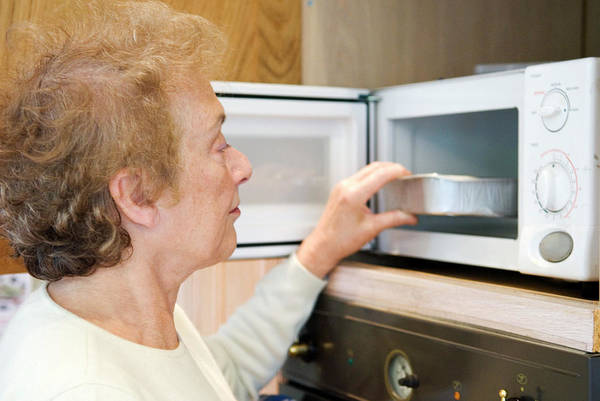 Elderly Woman Using A Microwave Oven Poster