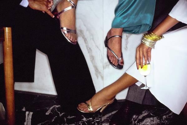 Models' Feet Wearing Metallic Sandals Poster