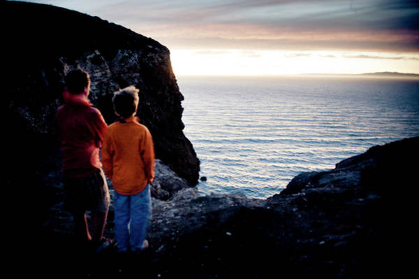 Two Men Watch The Sunset Over The Ocean Poster
