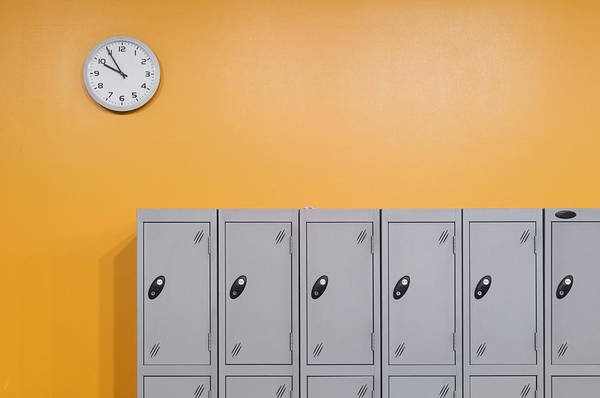 Clock On An Orange Wall Above Lockers Poster