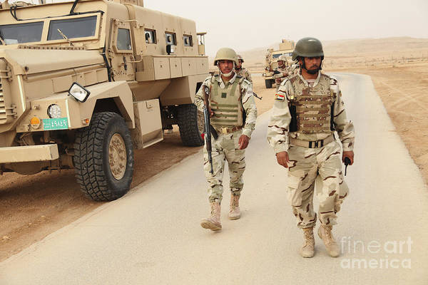 Iraqi Army Soldiers Walk Beside An Mrap Poster