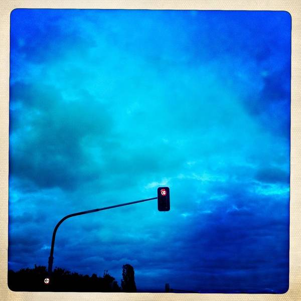 Red Traffic Light And Cloudy Blue Sky Poster