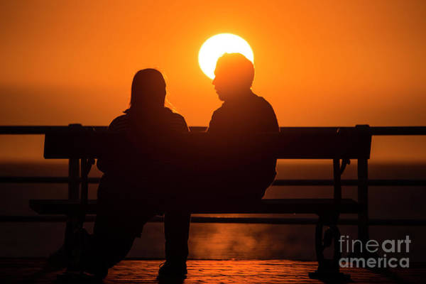 A Couple Sitting At Sunset Poster