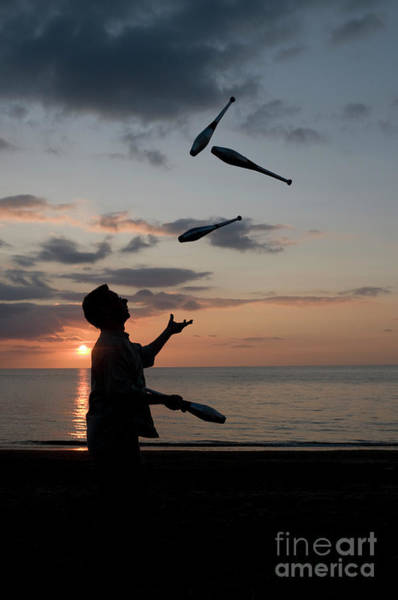 Man Juggling With Four Clubs At Sunset Poster