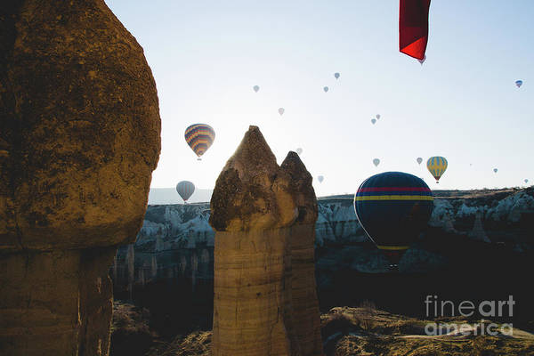 hot air balloons for tourists flying over rock formations at sunrise in the valley of Cappadocia. Poster
