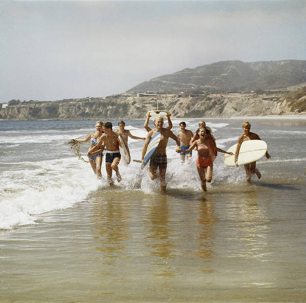 Group Of Surfers Running In Water With Poster