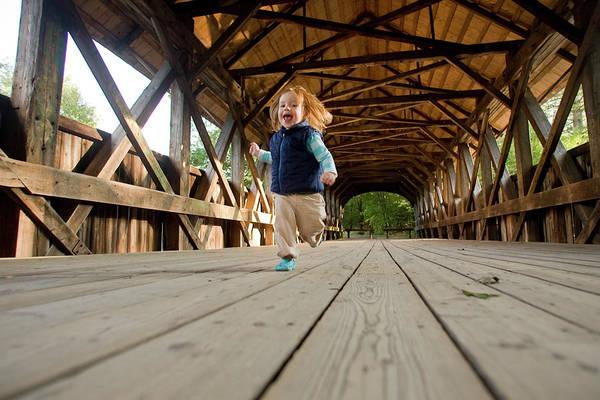Exuberance Photograph - A Little Girl Runs Across A Covered by Nick Lambert