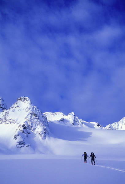 Wall Art - Photograph - A Man And Woman Ski Tour And Explore by Jimmy Chin