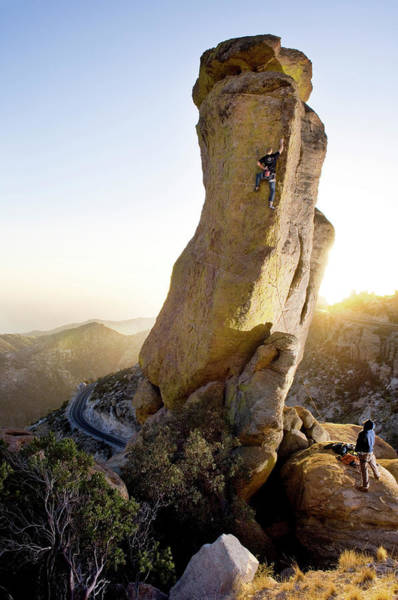 Scaling Photograph - A Man Climbs A Rock Tower At Sunset by Andrew Kornylak