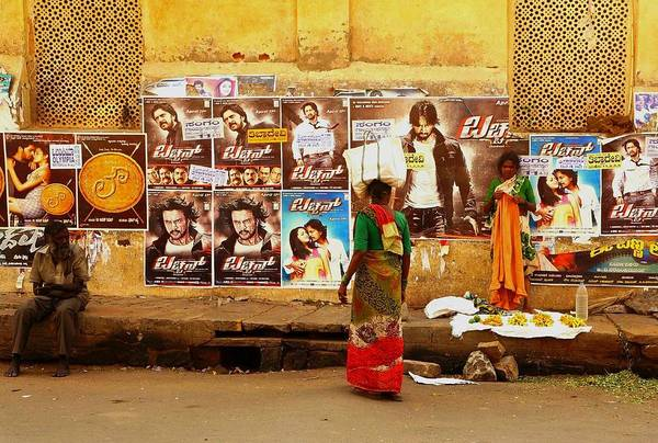Bollywood Wall Art - Photograph - A Woman In A Traditional Sari In Front Of A Wall Covered In Bollywood Posters In Mysore India - Niel by Niels Photography