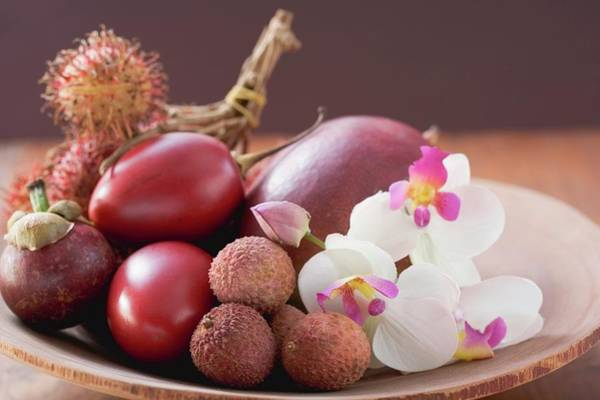 Wall Art - Photograph - Assorted Exotic Fruits In A Dish With Orchids by Foodcollection