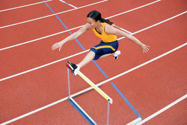 Agile Photograph - Athlete Jumping Over A Hurdle by Gustoimages/science Photo Library
