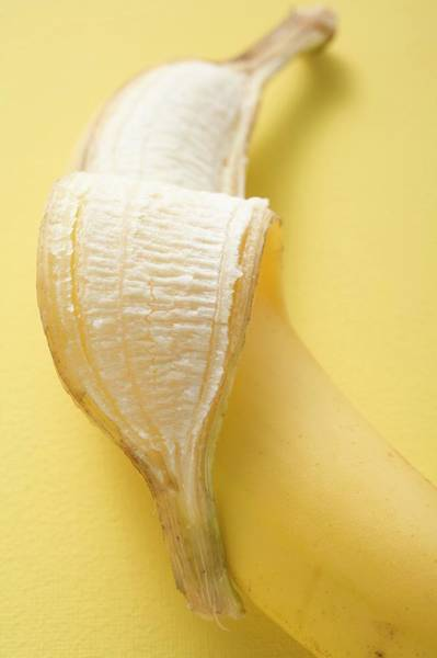 Wall Art - Photograph - Banana, Partly Peeled, On Yellow Background by Foodcollection