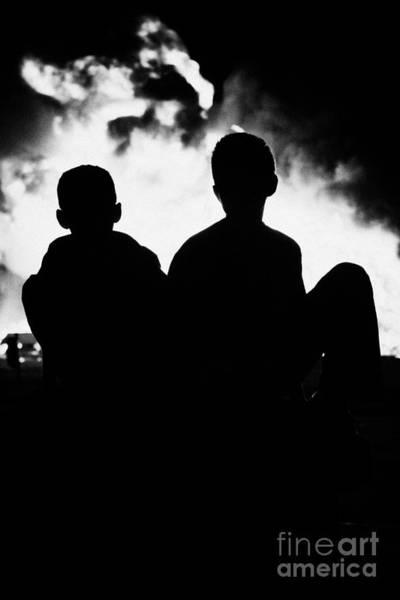 Wall Art - Photograph - children sitting watching 11th night bonfire in Monkstown by Joe Fox