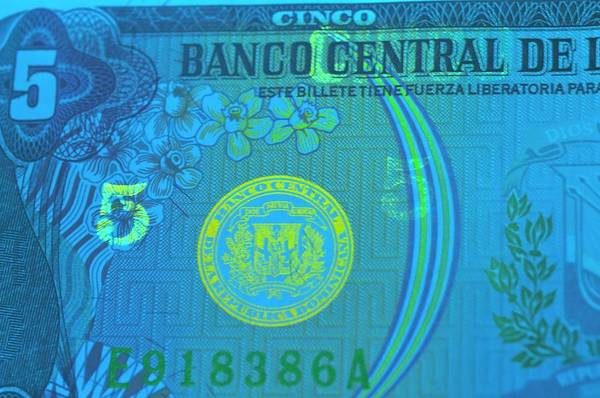 Dominican Republic Photograph - Dominican Republic Banknote In Uv Light by Louise Murray/science Photo Library