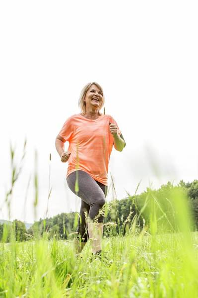 Wall Art - Photograph - Mature Woman Jogging In Grass by Science Photo Library
