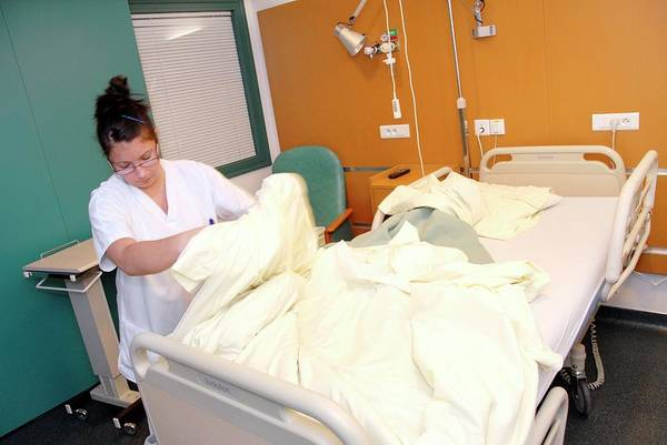 Wall Art - Photograph - Nurse Changing Hospital Bed Linen by Aj Photo/science Photo Library