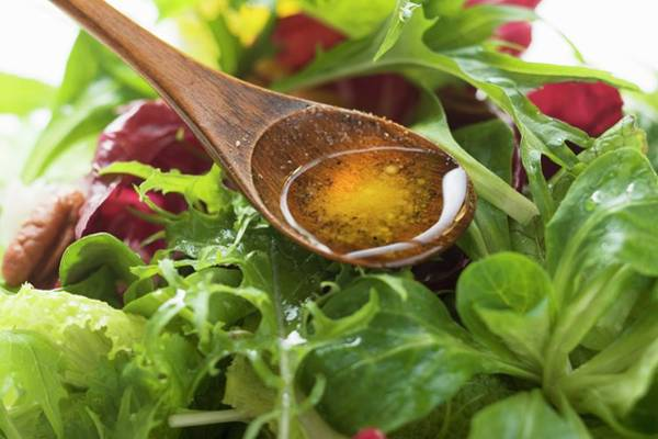 Salad Dressing Photograph - Olive Oil In Wooden Spoon Above Salad Leaves by Foodcollection