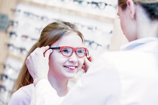 Wall Art - Photograph - Optometrist Trying Glasses On Girl by Science Photo Library