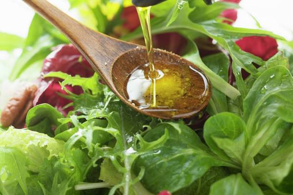 Salad Dressing Photograph - Pouring Olive Oil Into Wooden Spoon Above Salad Leaves by Foodcollection