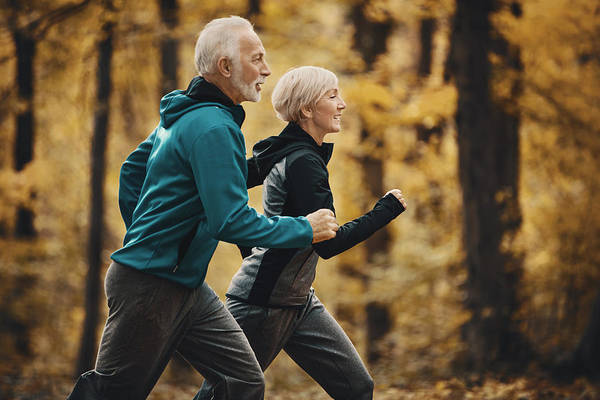 Senior Couple Jogging In A Forest. Art Print by Gilaxia