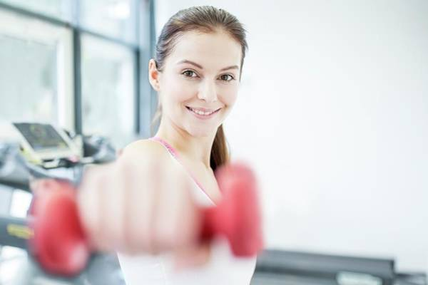 Self Confidence Photograph - Smiling Young Woman Holding Dumbbell by Science Photo Library