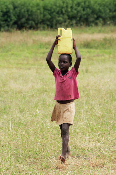 Wall Art - Photograph - Ugandan Boy Carrying Water by Mauro Fermariello/science Photo Library