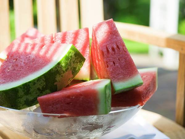 Watermellon Wall Art - Photograph - Watermelon Wedges In A Bowl Of Ice Cubes by Foodcollection