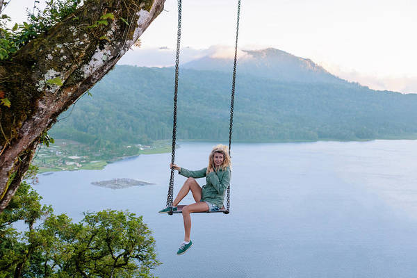 Wall Art - Photograph - Woman Sitting On Swing Against Lake by Konstantin Trubavin