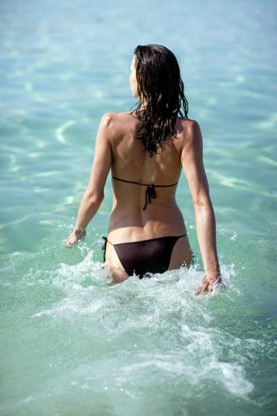 Sunbather Photograph - Woman Walking Into The Sea by Ian Hooton/science Photo Library