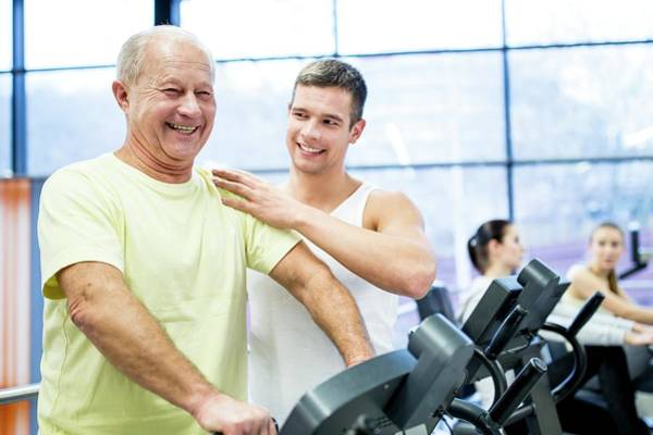 Self Confidence Photograph - Young Man Assisting Senior Man In Gym by Science Photo Library