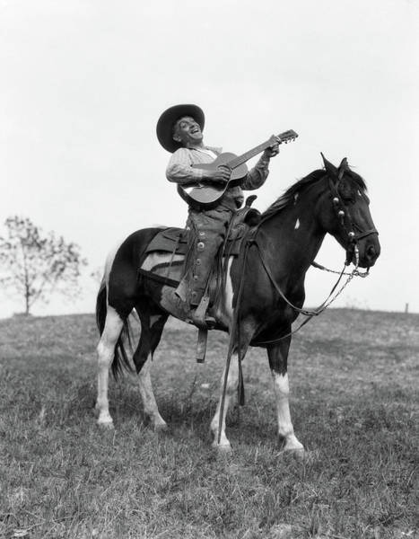 Strum Wall Art - Photograph - 1920s Cowboy On Horse Singing & Playing by Vintage Images