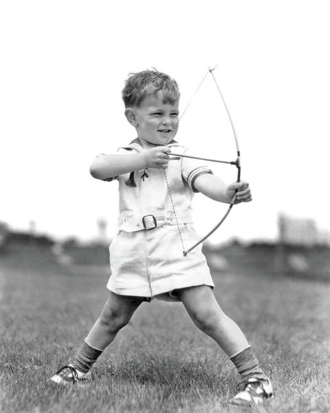 Archery Photograph - 1930s Boy Outdoors Aiming Toy Bow by Vintage Images