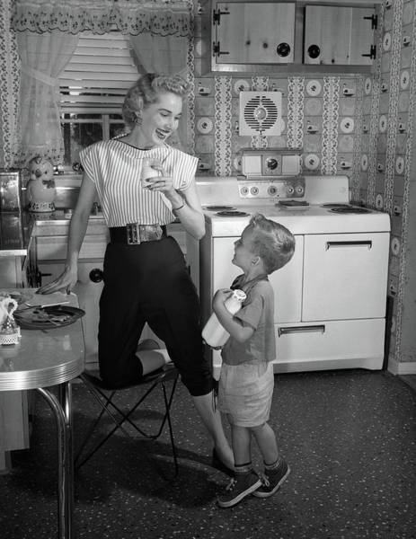 Parental Care Photograph - 1950s Boy In Kitchen Holding Bottle by Vintage Images