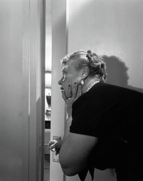 Sneak Photograph - 1950s Elderly Woman Opening Door by Vintage Images