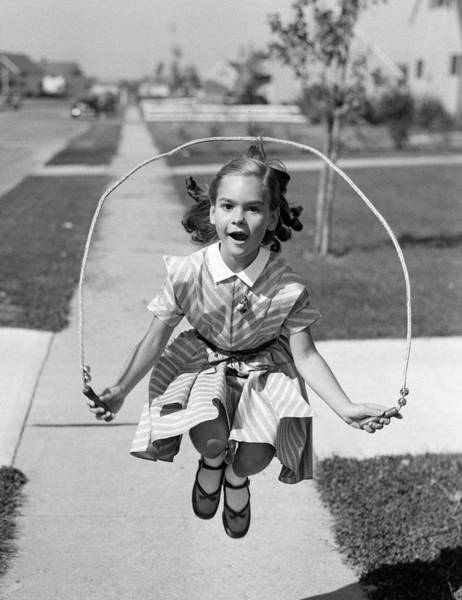 Agile Photograph - 1950s Girl Jumping Rope On Sidewalk by Vintage Images