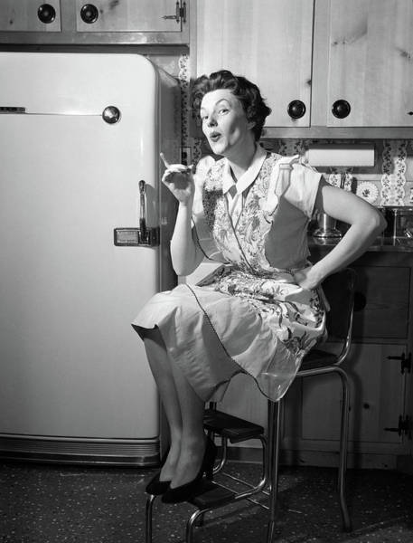 Wall Art - Photograph - 1950s Housewife Sitting On Stool by Vintage Images