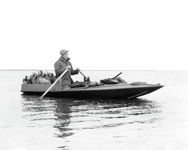 Duck Hunt Photograph - 1950s Man Duck Hunter Rowing Duck Boat by Animal Images
