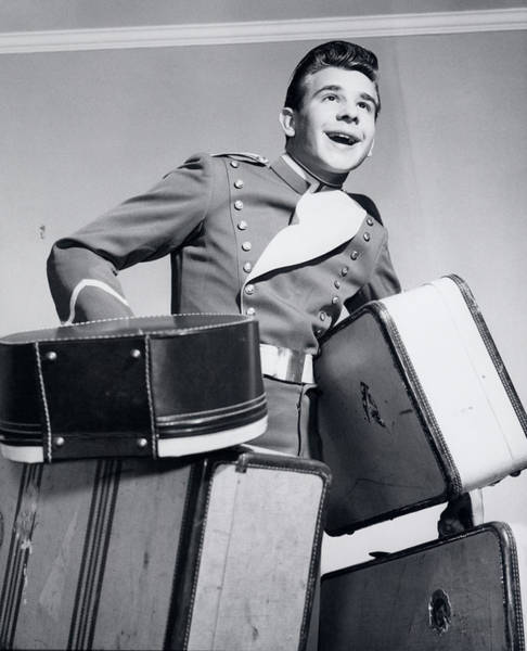 Porter Photograph - 1950s Smiling Bellboy Carrying Four by Vintage Images