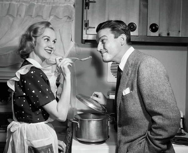 Making Love Photograph - 1950s Smiling Housewife At Stove Giving by Vintage Images
