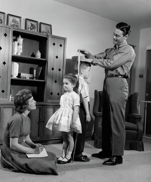 Parental Care Photograph - 1960s Father Measuring Daughter & Son by Vintage Images