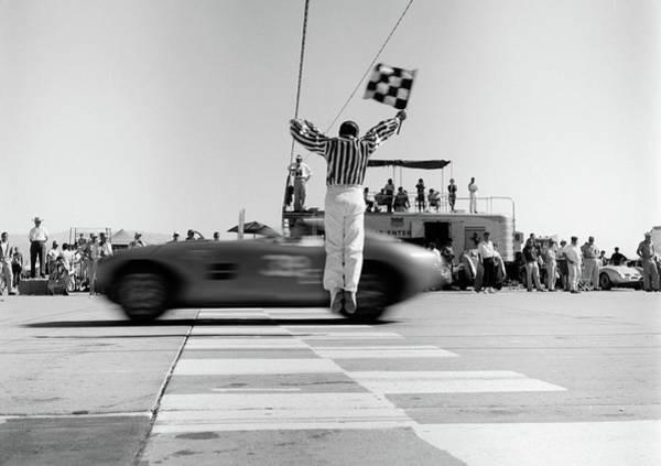 Motoring Photograph - 1960s Man Jumping Waving Checkered Flag by Vintage Images